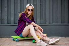 A pretty blond girl wearing sunglasses, checkered shirt and denim shorts is sitting on the bright logboards in front of royalty free stock photography