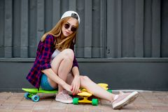 A pretty blond girl wearing sunglasses, checkered shirt and denim shorts is sitting on the bright logboards in front of stock photography