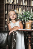 Pretty blond girl in a white dress in a retro interior Royalty Free Stock Image
