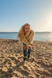 Pretty blond girl in a youth lifestyle suit on the beach laughing loudly and smiling. Happy blond girl in a youth lifestyle suit on the beach laughing loudly and Stock Photography