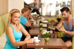 Pretty blond having coffee-break in gym Royalty Free Stock Image