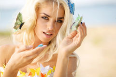 Pretty blond lady with colorful butterflies Royalty Free Stock Images