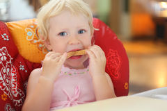 Pretty blond little girl eats bread Royalty Free Stock Photo