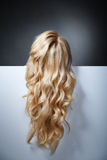 Pretty blond model hiding behind a big sheet of Royalty Free Stock Photos