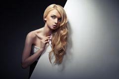 Pretty blond model hiding behind a big sheet of Royalty Free Stock Photo