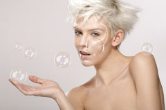 Pretty blond model plays with soap bubbles Stock Photography