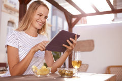 Pretty blond pointing at her tablet Stock Photography