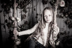 Pretty blond preteen girl with flowers. Pretty blond preteen girl sitting with flowers Stock Image