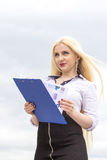 Pretty blond secretary writes somthing on documents outdoors. Stock Images