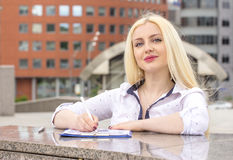 Pretty blond secretary writes somthing on documents outdoors. Stock Image