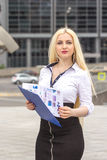Pretty blond secretary writes somthing on documents outdoors. Royalty Free Stock Images