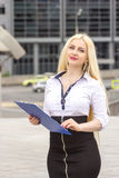 Pretty blond secretary writes somthing on documents outdoors. Stock Photography