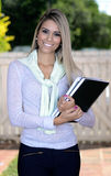 Pretty blond student. Beautiful blond woman smiling holding notepads Stock Image