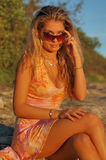 Pretty Blond With Sunglasses. Pretty blond young woman with sunglasses ,sitting on a rock Stock Photo
