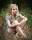Pretty Blond Teenager Sitting In The Grass Royalty Free Stock Photography