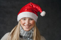 Pretty blond wearing christmas hat on dark Stock Photography