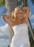 Pretty Blond Woman. In the tropics wearing a white dress Stock Images