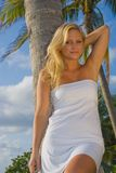 Pretty Blond Woman. In the tropics wearing a white dress Royalty Free Stock Photo