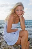 Pretty Blond Woman. In the tropics wearing a white dress Royalty Free Stock Images