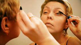 Pretty blond woman applying mascara make-up stock footage