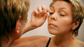 Pretty blond woman applying mascara make-up stock video