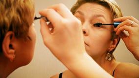 Pretty blond woman applying mascara make-up stock video footage
