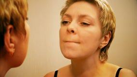 Pretty blond woman applying red lipstick make-up stock video