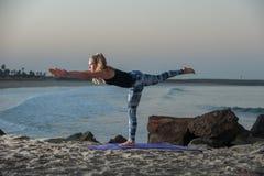 Pretty blond woman balancing on one leg near water. Stock Photos
