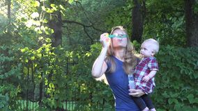Pretty blond woman blowing soap bubbles and beautiful baby child enjoy it in bright sun light. 4K stock footage