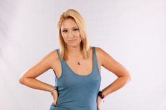 Pretty blond woman in blue shirt, looking at the camera. Woman in blue shirt and hands on hips looking at the camera with a grin stock photography