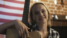 Charming young girl with guitar. Pretty blond woman in casual outfit embracing guitar and looking happily at camera
