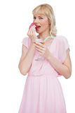 Pretty blond woman with cocktail eating fruits Stock Image