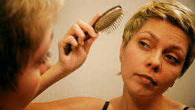 Pretty blond woman combs and brushes her hair stock video