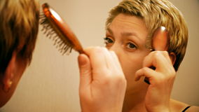 Pretty blond woman combs and brushes her hair stock video footage