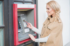 Pretty blond woman drawing money at an ATM Royalty Free Stock Images