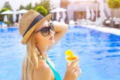 Pretty blond woman enjoying cocktail near the swimming pool Stock Photography