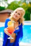 Pretty blond woman enjoying cocktail near a swimming pool royalty free stock photo