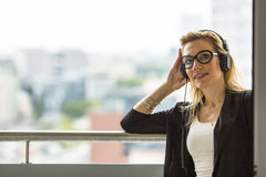 Pretty blond woman enjoys the music while standing on the balcony. Stock Photo