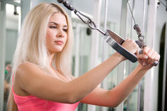 Pretty blond woman exercising on pulldown station. In gym Royalty Free Stock Photography