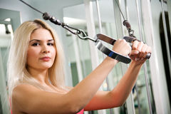 Pretty blond woman exercising on pulldown station. In gym Stock Images
