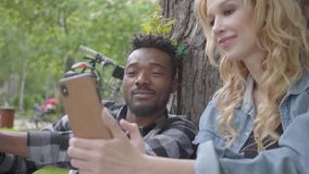 Pretty blond woman and handsome African American man sitting under an old tree in the park. The lady showing pictures to. Her friend on the cellphone The stock footage