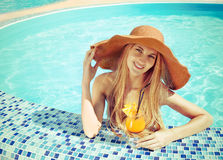 Pretty blond woman in a hat enjoying cocktail Stock Images