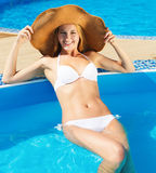 Woman in a hat enjoying a swimming pool Stock Image