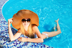 Wman in a hat enjoying a swimming pool Royalty Free Stock Photography