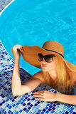 Woman in a hat enjoying a swimming pool Royalty Free Stock Image