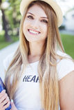 Pretty Blond Woman with Hat Holding a Book. Close up Pretty Young Woman with Long Blond Hair, Wearing Casual Shirt and Hat, Holding a Book and Smiling at the Royalty Free Stock Photo