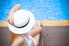 Pretty blond woman in a hat by a swimming pool Royalty Free Stock Photography