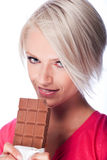 Pretty blond woman holding a bitten chocolate bar stock photography