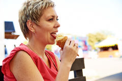 Pretty blond woman with ice cream Royalty Free Stock Photos