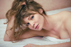 Pretty blond woman laying in bed Stock Images